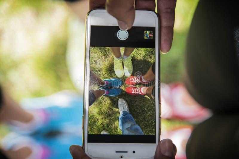 Некоторое молодые люди принимает ботинки изображения на телефоне в парке стоковое фото rf
