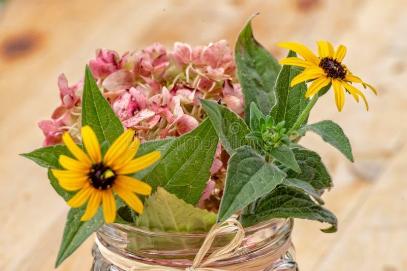 Некоторые желтые цветки в стекле стоковое фото rf