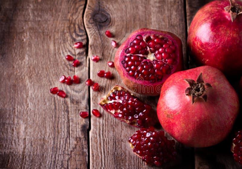 Некоторые красные гранатовые деревья на старом деревянном столе стоковая фотография