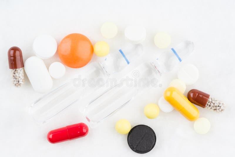 Некоторые пилюльки и 2 пробирки на медицинской таблице стоковое фото