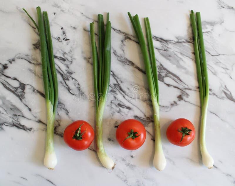 Некоторые свежие томаты и лук весны стоковое изображение