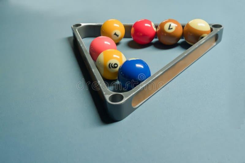 Некоторые шарики бассейна в шарике треугольника металла кладут на полку на бильярдном столе стоковое изображение