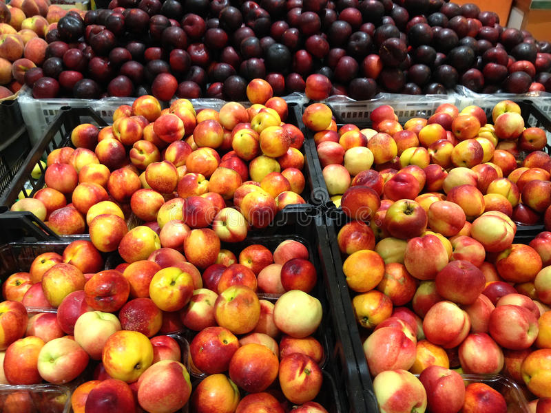 Нектарины и сливы плодоовощей лежа в коробках в супермаркете стоковые изображения