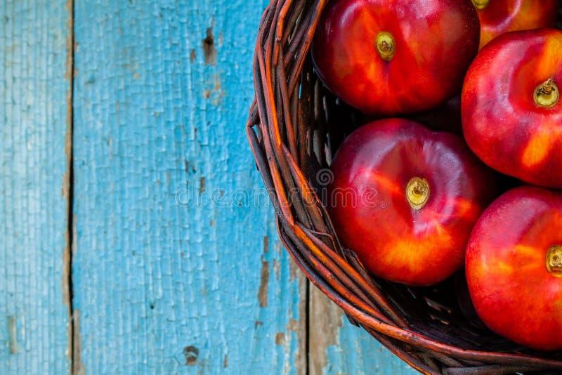 Нектарины свежих органических плоских нектаринов свежие органические плоские в корзине стоковые фото