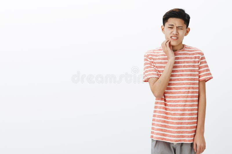 Неловкий привлекательный молодой азиатский студент имея щеку спада зуба касающую реагируя на боли, имеющ тухлые зубы стоковая фотография rf