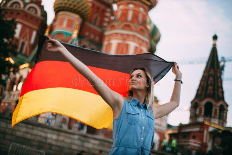 Немецкая девушка в России Немец развевая флаг стоковое фото