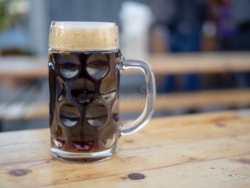 Немецкая стеклянная кружка пива заполнила с темным элем стоковое фото rf