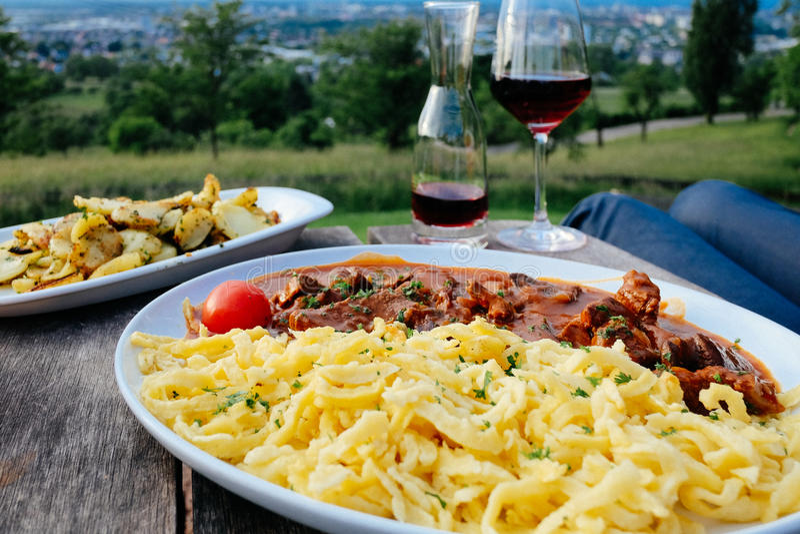 Немецкие лапши яичка - spatzle, вино, картошки на Jesuitenschloss, Фрайбурге, Германии стоковая фотография