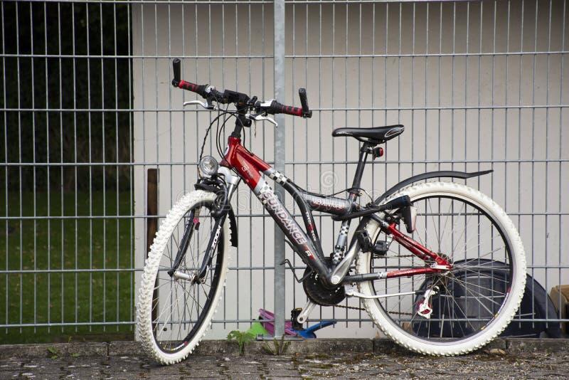 Немецкие люди останавливая и запереть горный велосипед на стальной загородке стоковые изображения rf