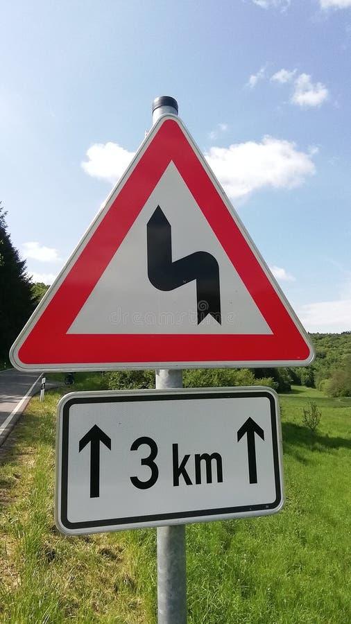 Немецкий дорожный знак предупреждая опасные кривые стоковые фото