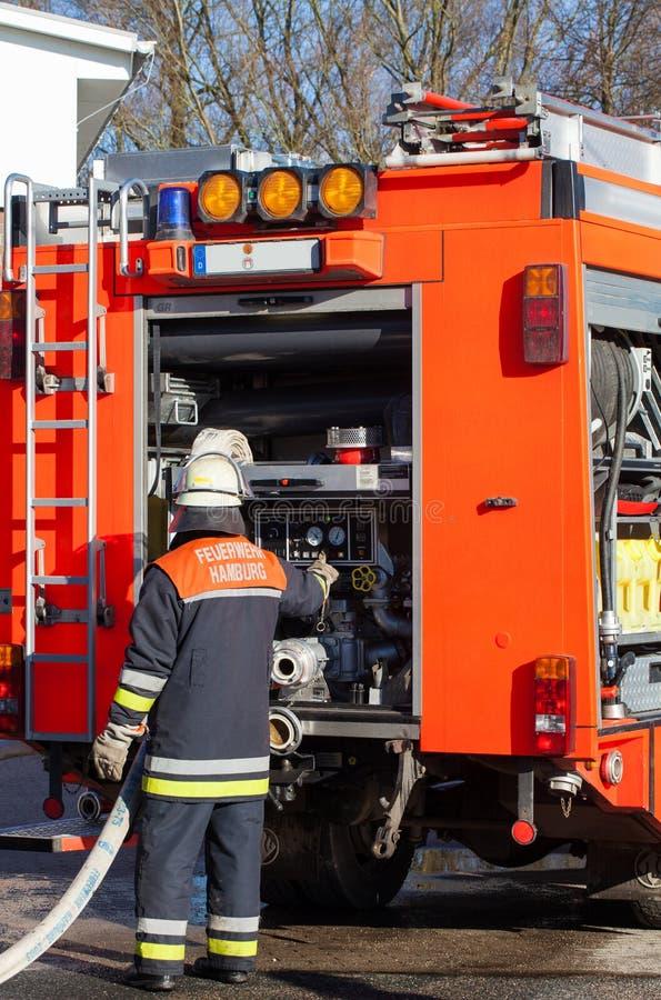 Немецкий пожарный перед аварийной машиной стоковые изображения