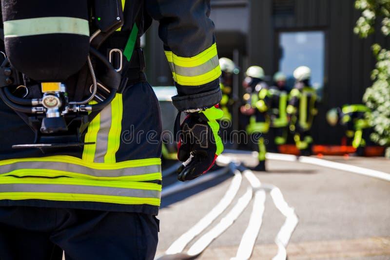 Немецкий пожарный Feuerwehr стоит около аварии стоковое фото