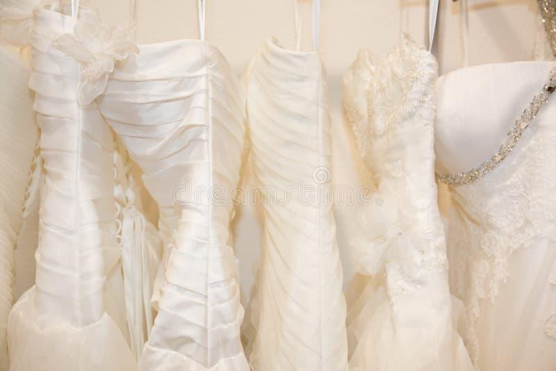 Немногие красивые платья свадьбы на вешалке стоковая фотография