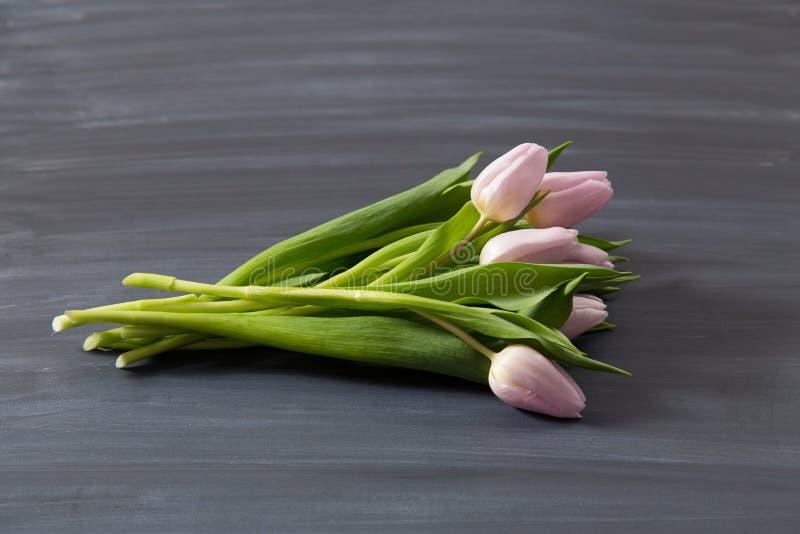 Немногие розовые тюльпаны цветут на темной поверхности chalcboard Букет на предпосылке конспекта нерезкости с космосом экземпляра стоковое фото