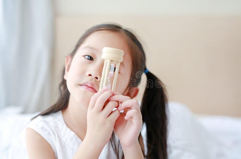 Немногое азиатская девушка держа sandglass в руке со смотреть через камеру Времена ожидания с часами стоковые фото
