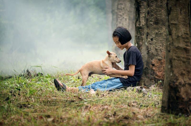 Немногое азиатская девушка сидя самостоятельно на зеленом поле под деревом с ее собакой, на открытом воздухе на сельской местност стоковое фото rf