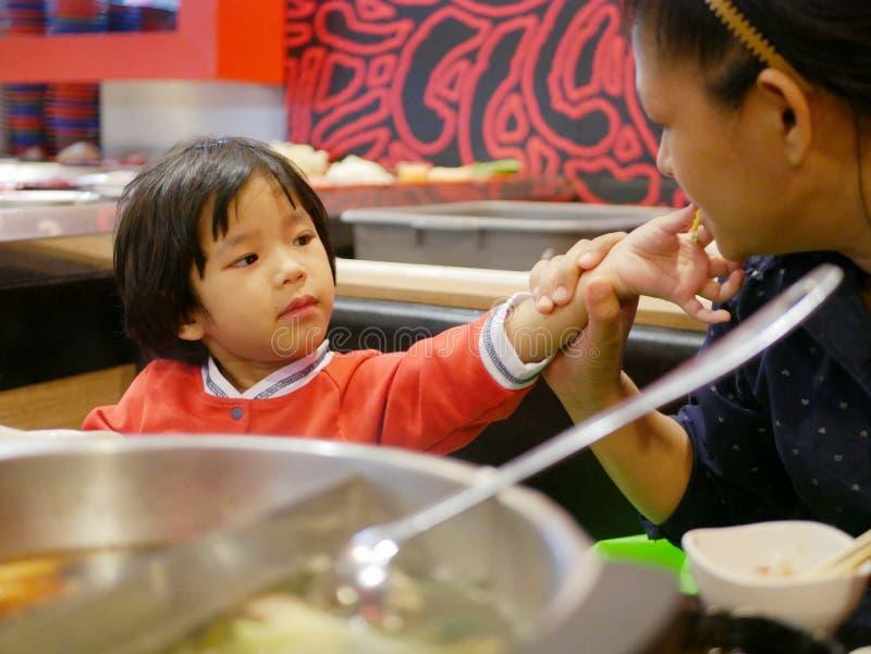 Немногое азиатский ребенок деля еду, hotpot, с ее матерью стоковая фотография