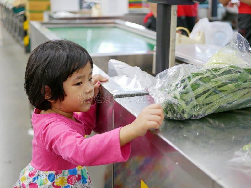 Немногое азиатский ребенок кладя китайскую славу утра в полиэтиленовый пакет на счетчик для весить и высчитывать цену стоковые изображения rf