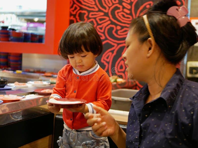Немногое азиатский ребенок наслаждается скомплектовать сырцовые ингредиенты, для ее матери, для hotpot варя, служа на двигая конв стоковое фото rf