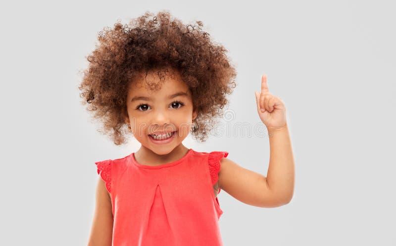 Немногое Афро-американская девушка указывая палец вверх стоковое изображение