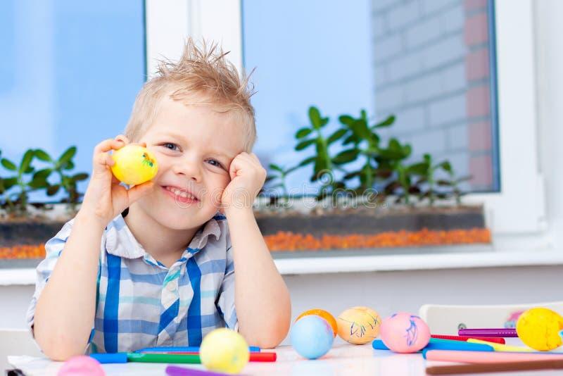 Немногое белокурый мальчик подготавливает для пасхи и крася яя цветастые отметки Концепция пасхи и праздников стоковая фотография