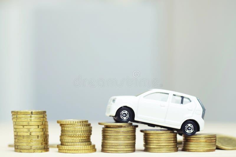 Немногое белый автомобиль над много монетками и предпосылкой штабелированными деньгами стоковое фото rf