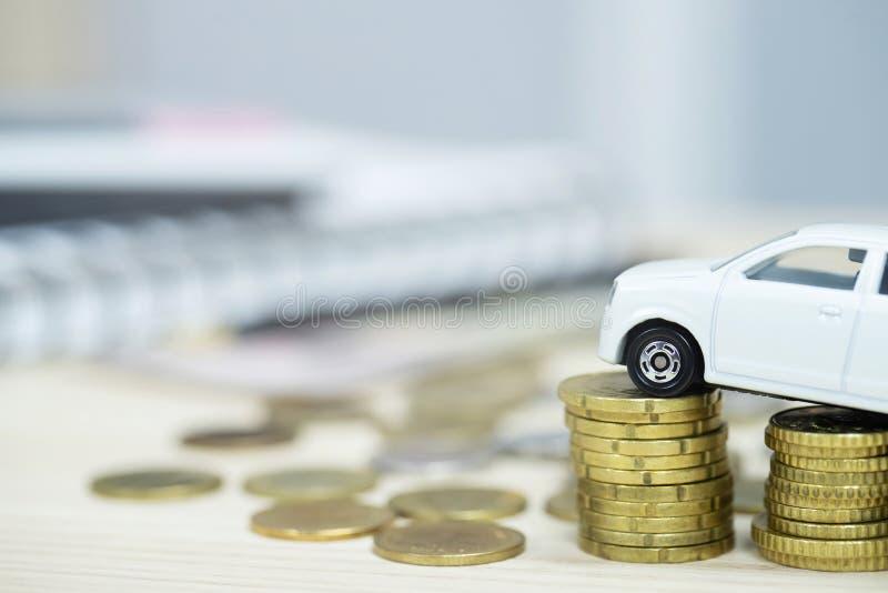 Немногое белый автомобиль над много монетками штабелированными деньгами для банковских ссуд стоит финансы стоковые фото