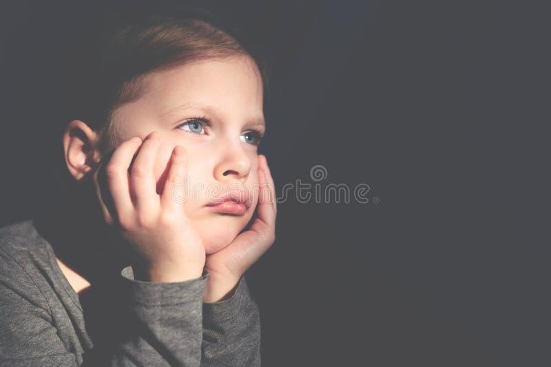 Немногое грустная девушка сидя и подпирая ее голова с ее руками стоковое изображение