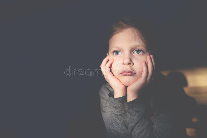 Немногое грустная девушка сидя и подпирая ее голова с ее руками стоковое фото rf