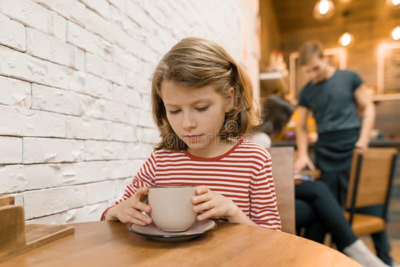 Немногое девушка ребенка в кафе с большой чашкой напитка искусства стоковая фотография