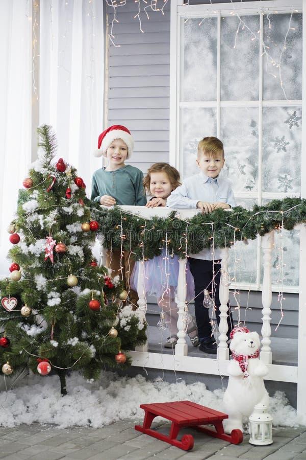 Немногое дети в ожидании Новый Год и рождество 3 маленького ребенка имеют потеху и играют около рождественской елки стоковые изображения