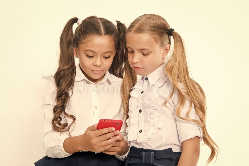 Немногое дети зависит от мобильного телефона Девушки отправляют SMS sms с мобильным телефоном зависите стоковая фотография