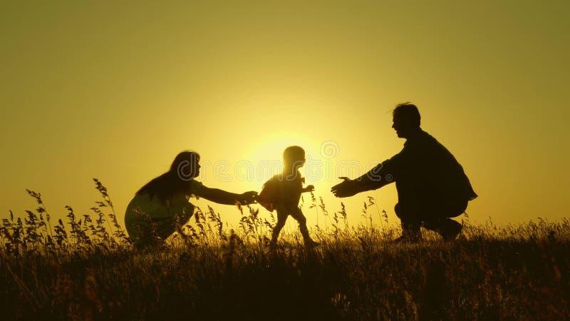 Немногое дочь с родителями скача на заход солнца Силуэты папы и младенца мамы в лучах рассвета r стоковое фото rf