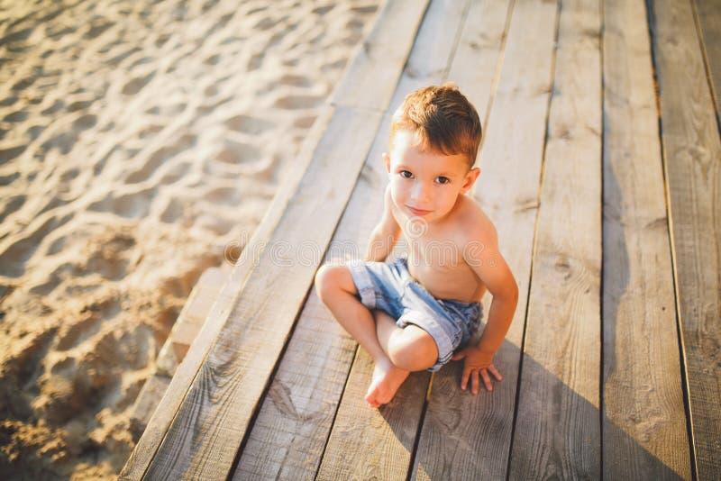 Немногое кавказский ребенок мальчика сидя на деревянном песчаном пляже пристани, лете, каникулах моря около воды Тема подача врем стоковая фотография rf