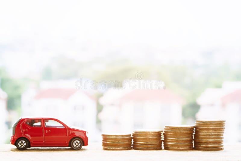 Немногое красный автомобиль над много монетками штабелированными деньгами стоковое фото