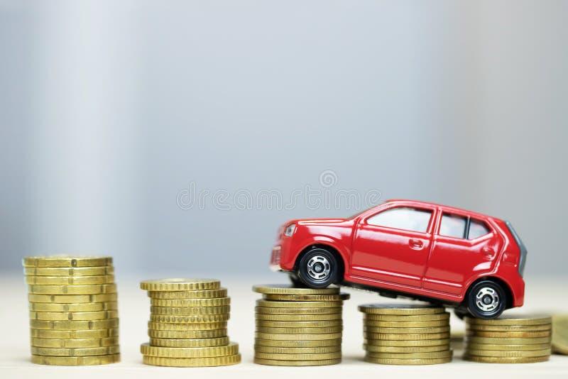 Немногое красный автомобиль над много монетками штабелированными деньгами для банковских ссуд стоит финансы стоковое фото rf
