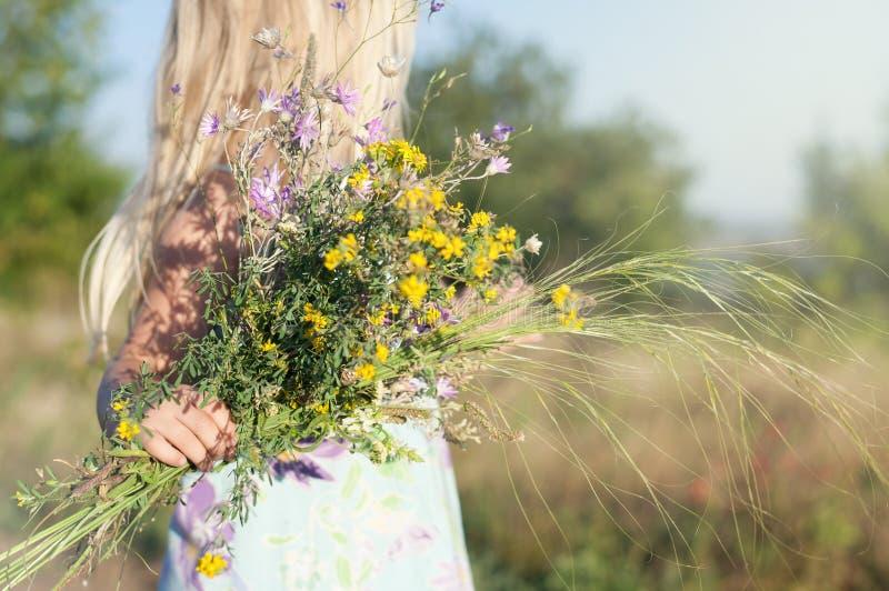 Немногое милая белокурая девушка в поле на солнечный день с букетом полевых цветков стоковые изображения rf