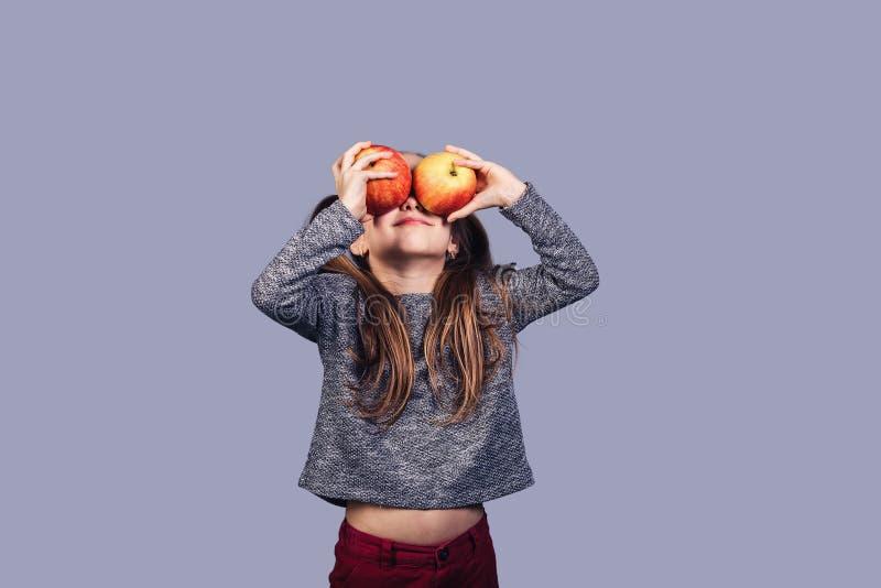 Немногое милая девушка закрывает ее глаза с 2 яблоками стоковые изображения