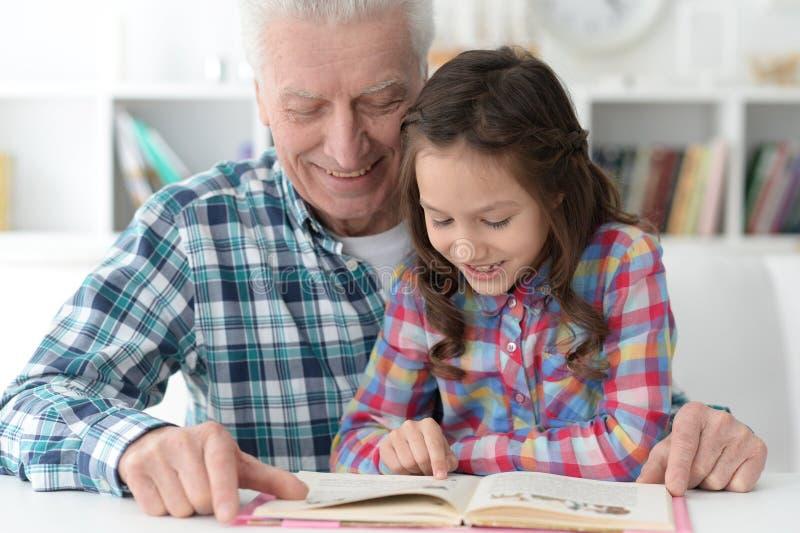 Немногое милая девушка с книгой чтения деда стоковые фотографии rf