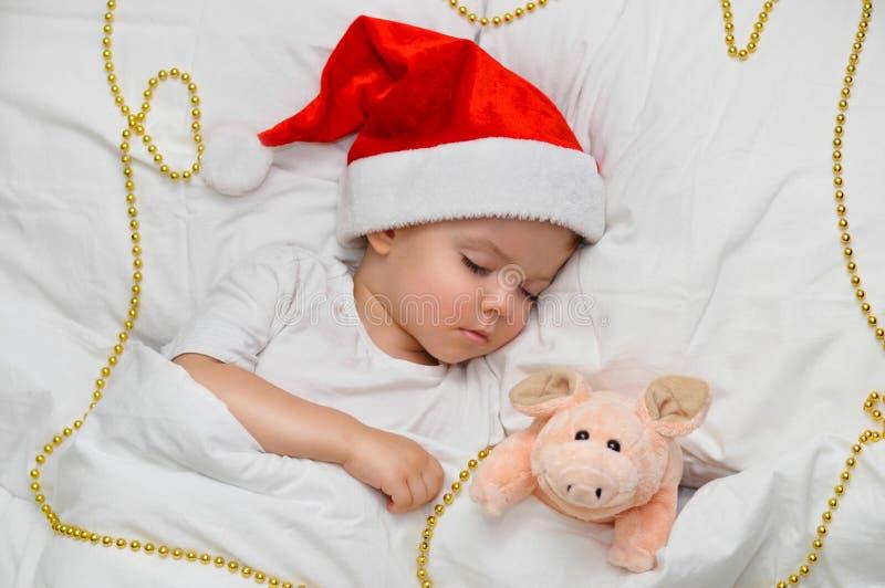 Немногое младенец спать на белом белье в шляпе Санта с его свиньей игрушки, которая символ года 2019 стоковые изображения rf