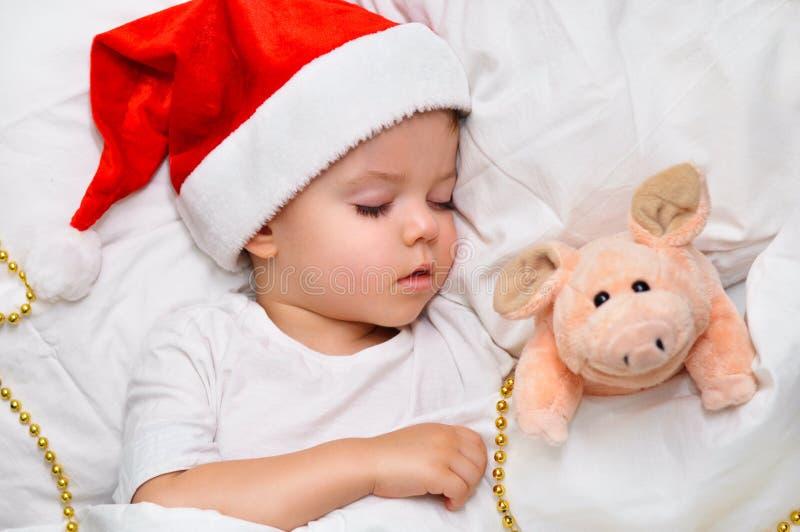 Немногое младенец спать на белом белье в шляпе Санта с его свиньей игрушки, которая символ года 2019 стоковая фотография rf
