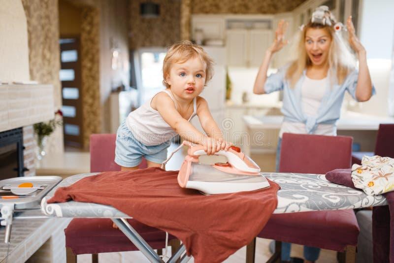 Немногое одежды утюгов младенца, домохозяйка в ужасе стоковое фото rf
