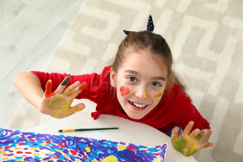 Немногое ребенок с покрашенными руками и смотреть на на таблице внутри помещения стоковые фото