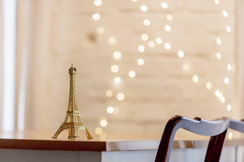 Немногое сувенир Эйфелевой башни на таблице со светами рождества стоковые изображения