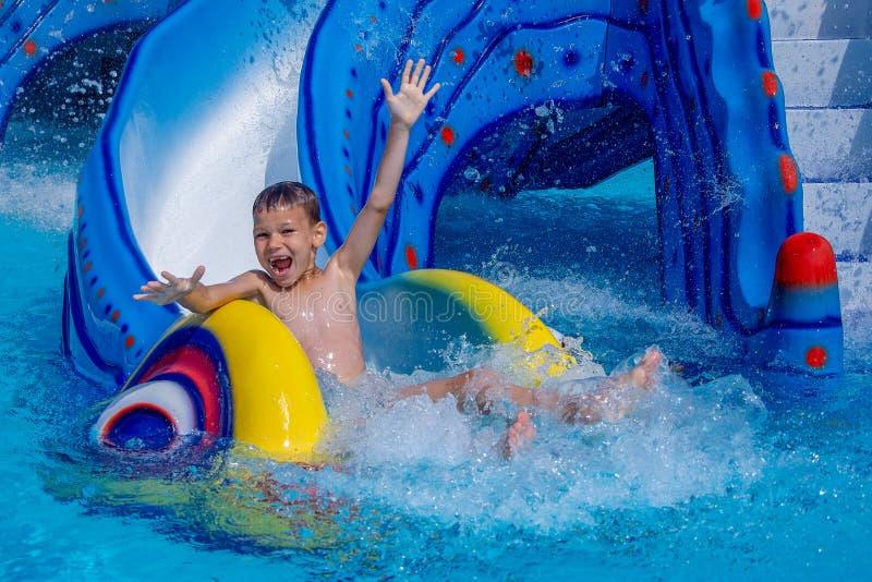 Немногое счастливый мальчик с руками вверх по сползать в воду в парке aqua стоковая фотография rf