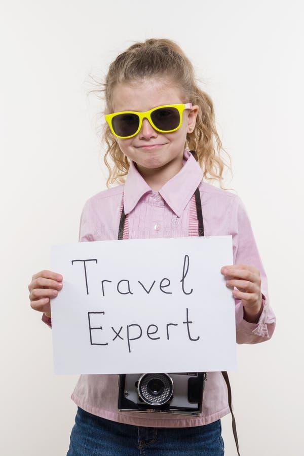 Немногое туристский специалист, девушка ребенка с камерой фото в солнечных очках держа белый лист бумаги со специалистом перемеще стоковое фото rf