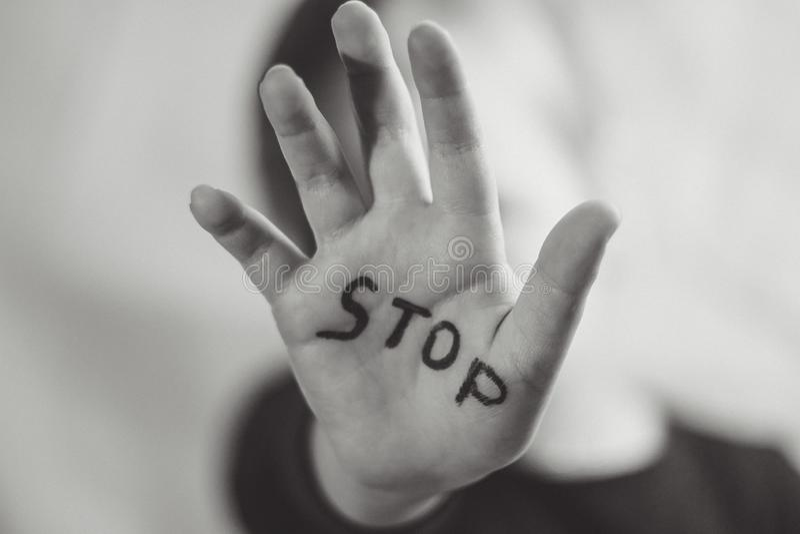 """Немногое устрашенная девушка показывает слово """"стоп """"написанный на руке Дети подвергаются к насилию и опубликовывать в доме и стоковая фотография"""