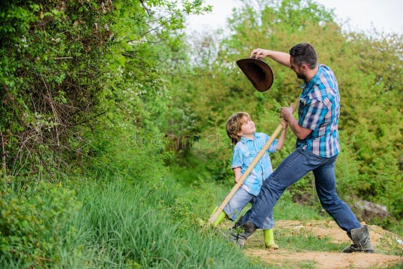 Немногое хелпер в саде Милый ребенок в природе имея папы ковбоя потехи Найдите сокровища Мальчик и отец с лопаткоулавливателем стоковые изображения