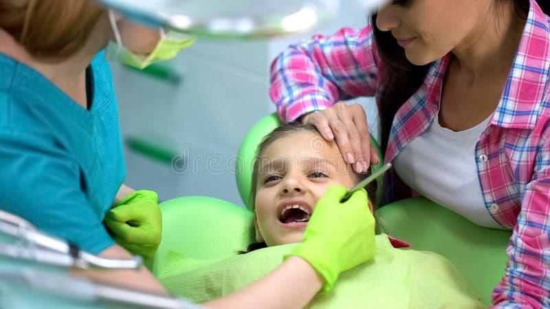 Немногое храбрая девушка посещая педиатрическое stomatologist, рассмотрение зубов молока стоковое фото rf