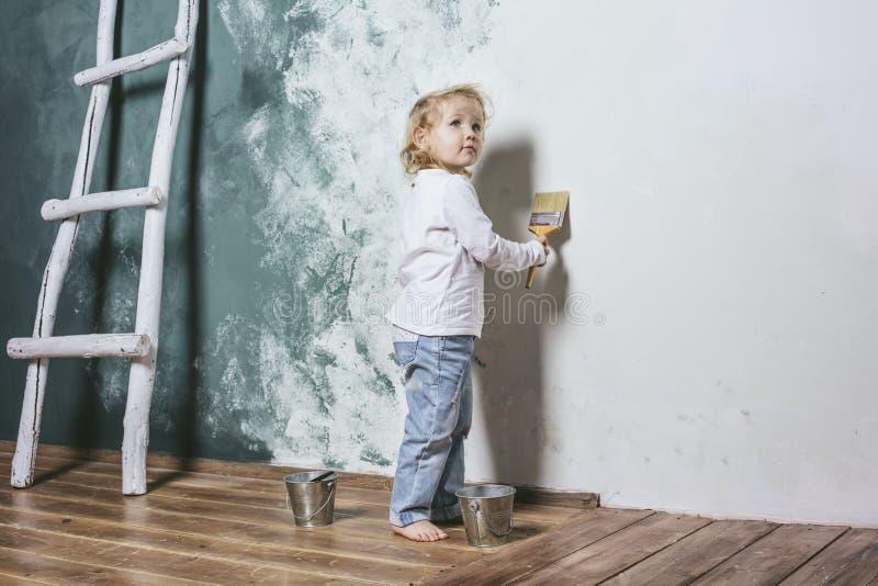 Немного красивый и счастливый ребенок в джинсах красит стену с br стоковая фотография